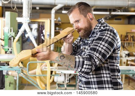 Craftsman inspects a guitar neck in a workshop for wood. Hard working man with tattoo and beard working with musical instruments.