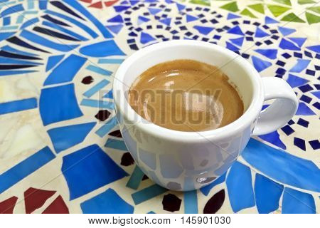 cup of coffee in a white cup on mosaic table in street cafe