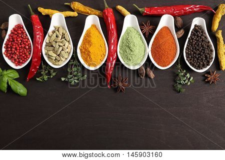 Colorful aromatic Indian spices and herbs on a wooden background.