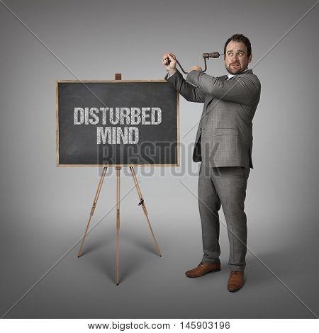 Disturbed mind text on blackboard with businessman drilling his head
