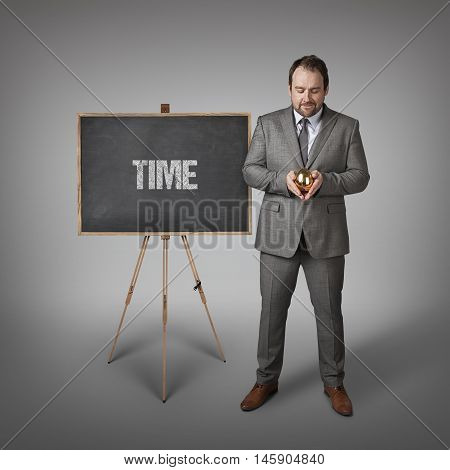 Time text on  blackboard with businessman and golden egg