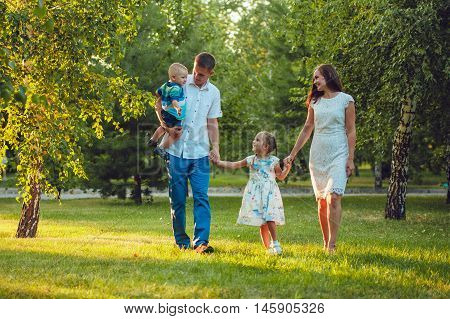 Happy young family of four people walking and having fun in the park