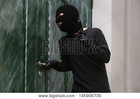Armed thief breaking a door