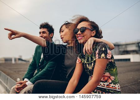 Shot of young woman showing something to her friends while sitting on terrace. Friends sitting on rooftop and enjoying the view.