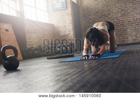 Woman On Exercise Mat Doing Stretches At Gym