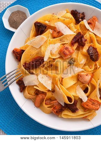 Italian Fettuccine pasta with salmon parmesan and dried tomatoes. Shot from above