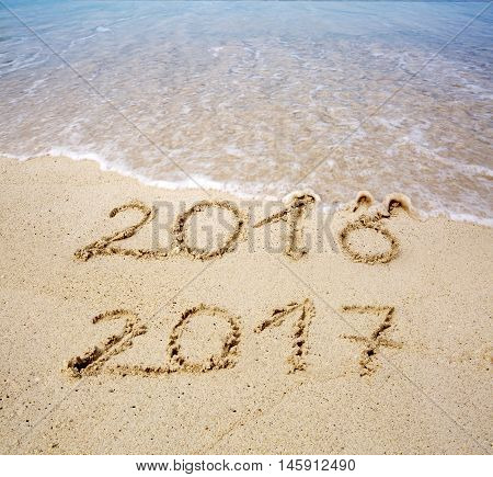 2016 2017 inscription written in the wet beach sand with sea water wave. Inscription 2016 and 2017 on a beach sand, the wave is almost covering the digits 2016.