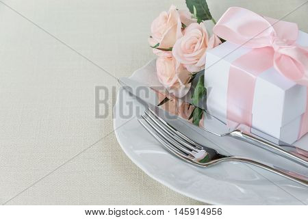 Beautiful decorated table with white plates gift box with a pink ribbon cutlery and pink rose flowers on tablecloths with space for text