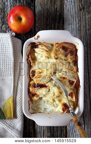 Gratin of potatoes apples and Camembert cheese on wooden table