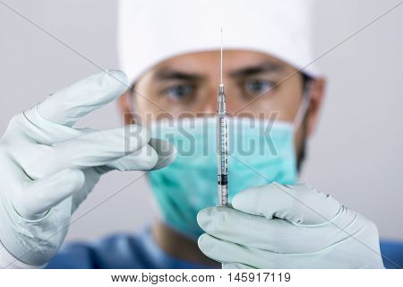 doctor surgeon with syringe in front of face