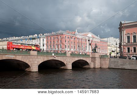 SAINT - PETERSBURG, RUSSIA - SEPTEMBER 5, 2016: Hop-On Hop-Off. City Tour Bus rides on The Anichkov Bridge with The Horse Tamers by Peter Klodt across The Fontanka River near Nevsky Avenue