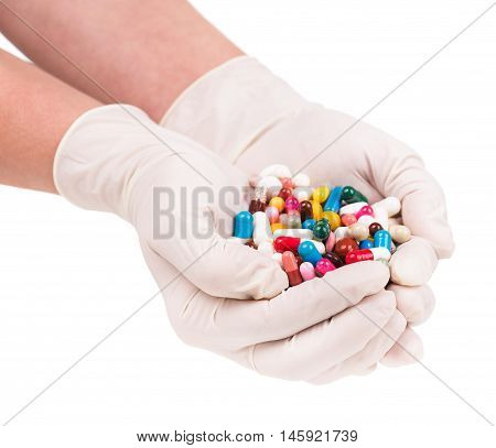 Female doctor's hand holding pills isolated over white background