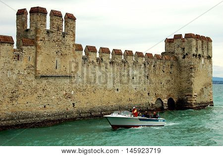 Sirmione Italy - June 1 2006: Speedboat cruises past the imposing defense walls of 13th century Scaligers' Castle (Rocca Scaligera) built over the waters of Lake Garda