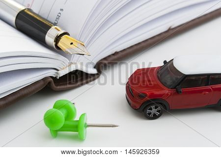 Pen business notebook. The handle is in a notebook. Registration of insurance on the car. on car expenses. The costs of the transport company. Nearby lies a toy car out of a chocolate egg.