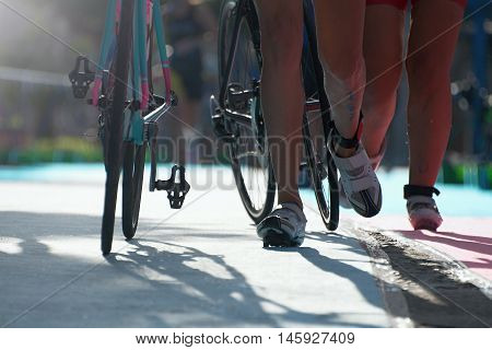 Triathlete running with cycle in the transition zone
