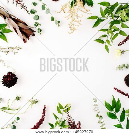 creative decorated and arranged flat lay frame concept with green and purple branches on white background. top view