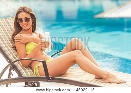 Pretty girl in green swimwear and sun glasses is applying cream on her shoulders and smiling while sunbathing on the chaise longue near the pool