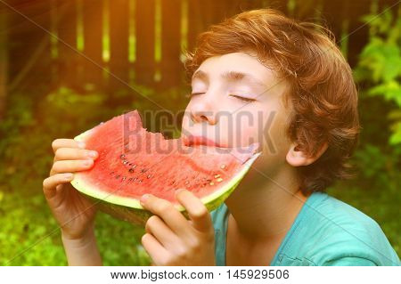 preteen boy bite water melon slice with closed eyes on the sunny summer garden background close up portrait