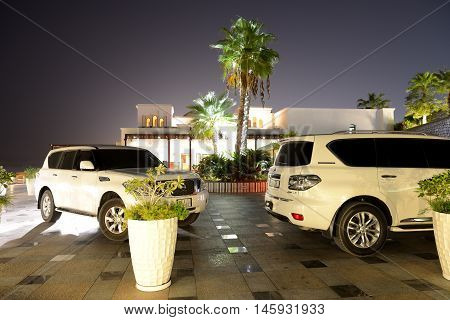 RAS AL KHAIMA UAE - SEPTEMBER 7: The luxury off-road cars are near luxurious hotel on September 7 2013 in Ras Al Khaima United Arab Emirates. Up to 10 million tourists have visited UAE in year 2013.