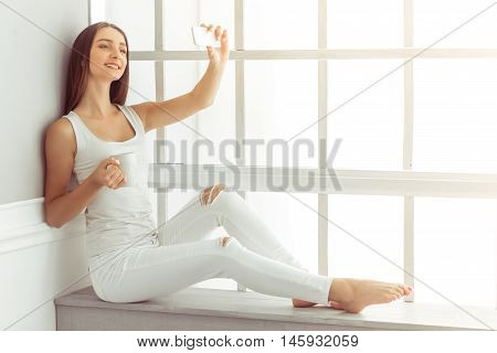 Attractive young girl in white casual clothes is making selfie using a smart phone holding a cup and smiling while sitting on the window sill at home