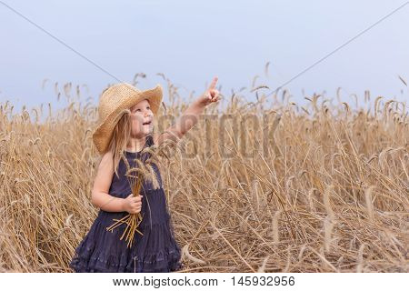 Baby girl in a big straw hat standing in a wheat field with a bunch of ears and hand points in the sky birds.