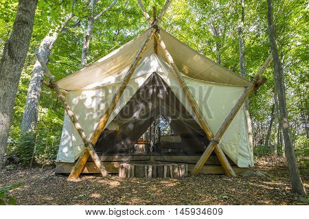 Luxury Camping Tent Made of White Canvas and Cedar Posts in the Woods