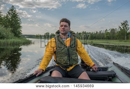 Brave handsome man is operating of boat on the river