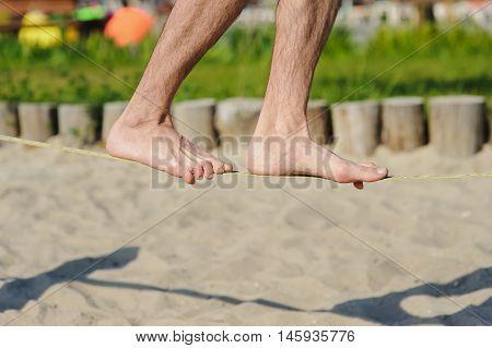 Man walking on the sling. Young man balancing on slackline at a beach.