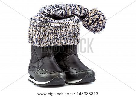 Cold winter clothing and shoes - a motley knitted hat or cap and black boots isolated on white background.