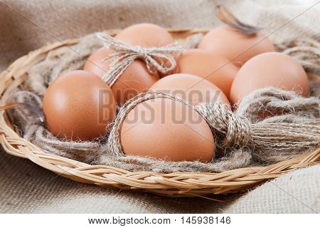Eggs in a basket on a canvas sack.