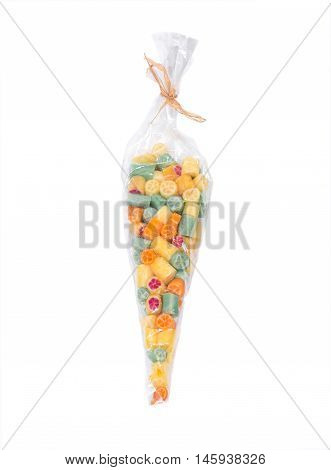 Hard home made all natural candies in skinny plastic sleeve on white background