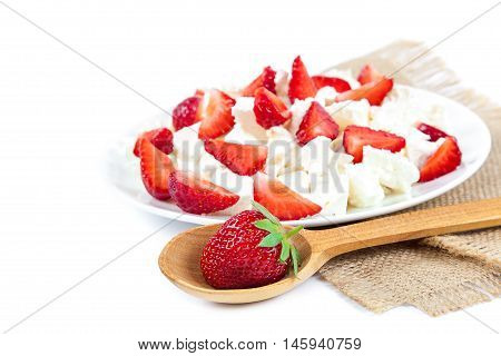 Fresh strawberries with cottage cheese and wooden spoon isolated on a white background.