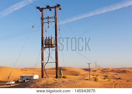 UNITED ARAB EMIRATES, 3 APRIL 2016. Editorial Photograph of Uneven Row of Electricity Pylons Stretching Across the Shifting Sands of the Desert