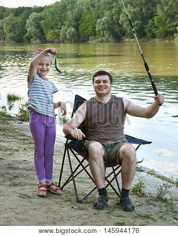people camping and fishing, family leisure in nature, fish caught on bait, river and forest, summer season