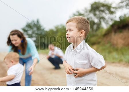 Boy throwing rocks into the river during a family vacation