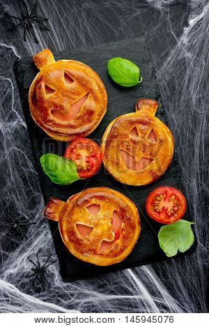 Vegetarian pumpkin mini pizzas to Halloween party treats on black background with spider web