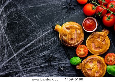 Halloween pizza idea - homemade calzone shaped a pumpkin with ham cherry tomatoes and basil black background with spider web empty space for text