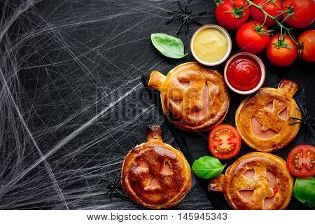Jack-o'-Lantern vegetables ham snack patties for Halloween party black background with cobweb empty space for text