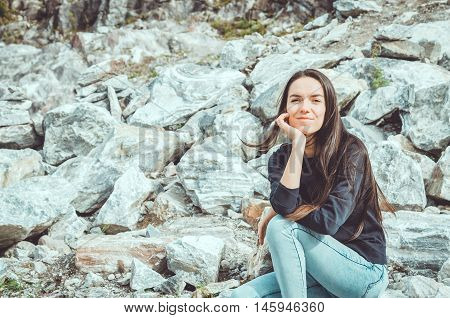 Portrait of young woman in national Highland Park Ruskeala in the Republic of Karelia Russia. Russian tourism concept. Young brunette female with long hair sitting on big grey stones and looking at camera.