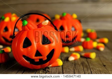 Halloween Jack O Lantern Candy Holders Close Up With Scattered Candy On Rustic Wood