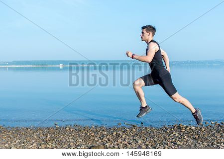 Sports, Fitness. Fit man running workout jogging at beach. Outdoors training