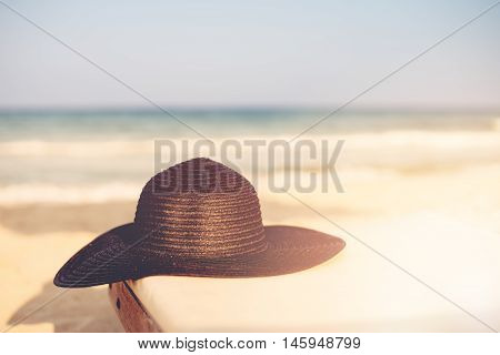 Black Hat On Beach Chair On The Tropical Sand Beach. Sun, Sun Haze, Glare. Copy Space