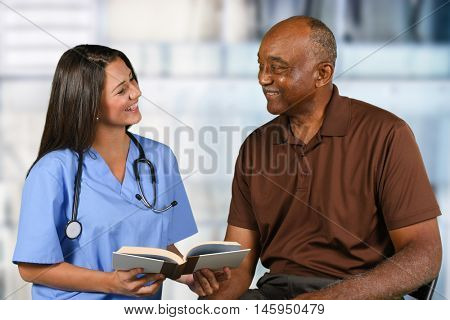 Health care worker helping an elderly patient read a book