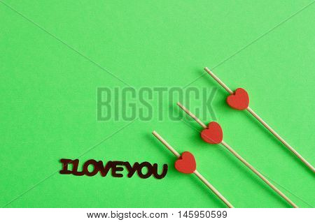 Valentine's Day. Three red hearts on sticks with a green background an I love you in red lettering