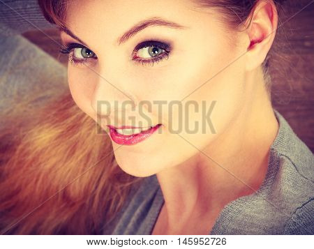 Beauty makeup fashion relax leisure concept. Young cheerful lady lying on floor. Smiling woman posing indoors on wooden background.