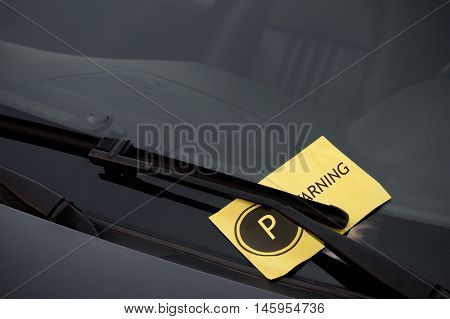 Parking ticket on the windshield of a dark car