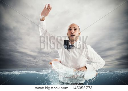 Businessman at sea with life preserver for help