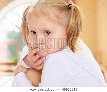 The concept of pre-school education of the child among their peers . in gaming room with a large arched window.Beautiful little blonde girl with pigtails on his head, white t-shirts without a pattern. The girl is upset about something. Close-up.