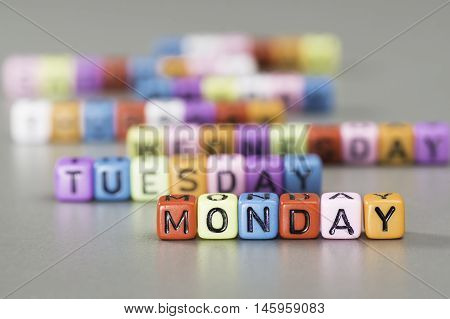 Monday text, name of the day written on colorful dice