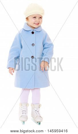 Cute little girl figure skater in a blue coat and a white cap is standing on skates with two blades-Isolated on white background